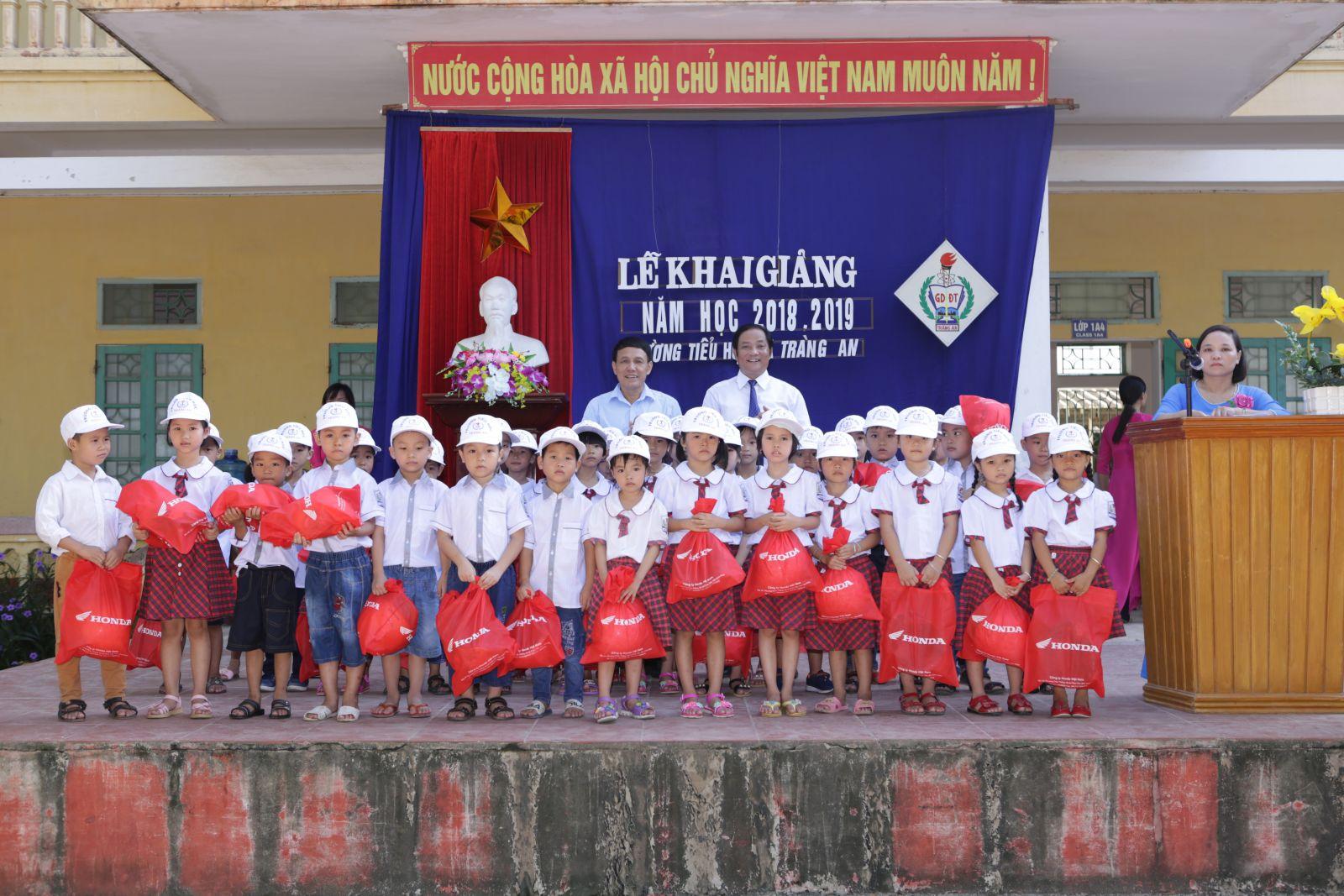 Học sinh lớp 1 nhận mũ bảo hiểm nhân ngày khai trường
