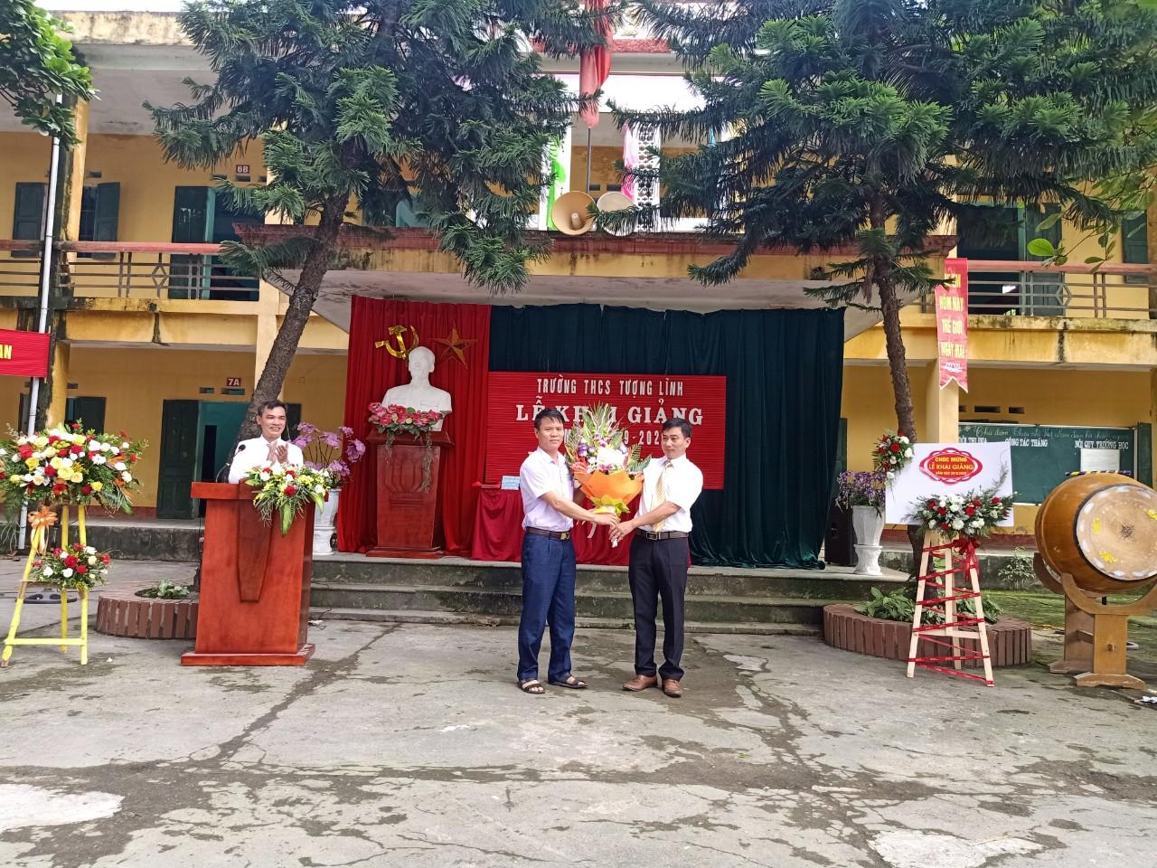 Ông: Trần Văn Tiên - Phó bí thư Đảng ủy xã tặng hoa cho lãnh đạo nhà trường