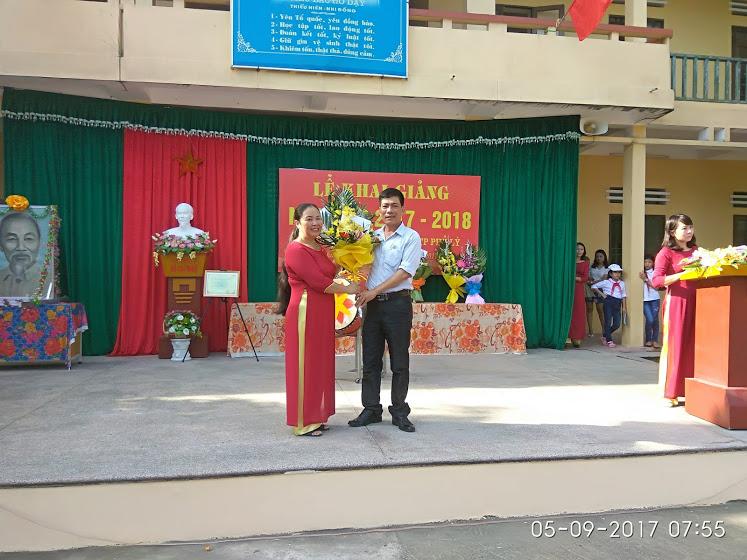 Đồng chí Bùi Văn Tuấn - Bí thư Đảng ủy, Chủ tịch HĐND phường tặng hoa chúc mừng nhà trường